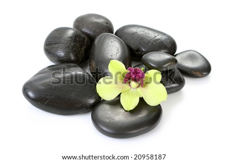 black pebbles with yellow orchid isolated on white