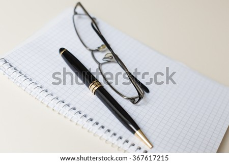 black pen and glasses with white pad or notepad on ivory table