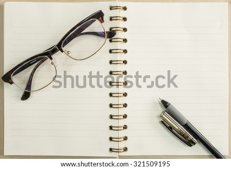 Black pen and notebook with eyeglasses background