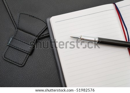 Black pen on blank notepad or planner with suitcase signifying concepts such as office and business, and work related objects - stock photo
