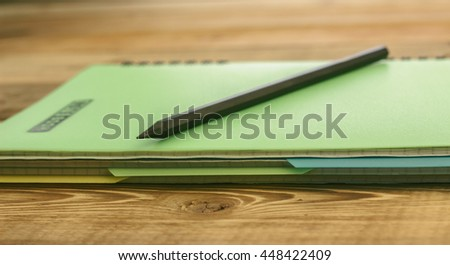 Black pencil on closed notebook with bookmarks lying on a wooden table