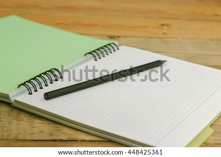 Black pencil on notebook with bookmarks lying on a wooden table