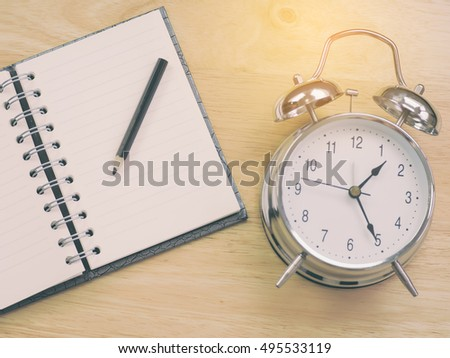 Black pencil on notebook with silver alarm clock