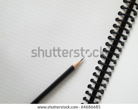 Black pencil on open white paper note book top view - stock photo