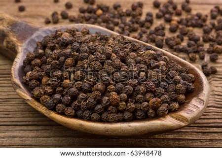 Black pepper and very old wooden spoon - stock photo
