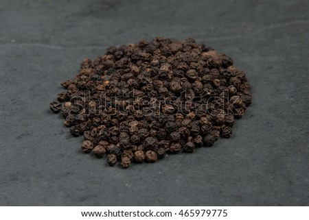 Black pepper corns on grey slate table