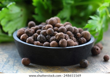 black pepper flavored spice on a wooden table - stock photo