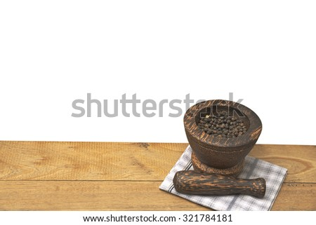 Black pepper in wooden mortar with pestle lay on napkin over old wooden table isolated on white - stock photo