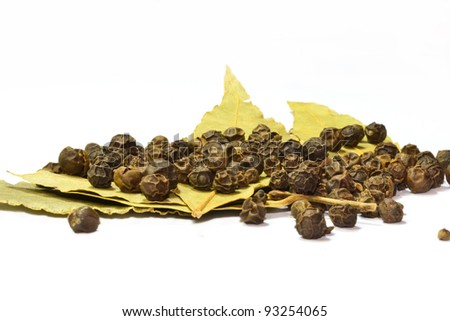 black pepper on bay leaf isolated on the white background - stock photo