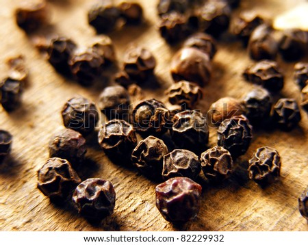 Black pepper on wood background - stock photo