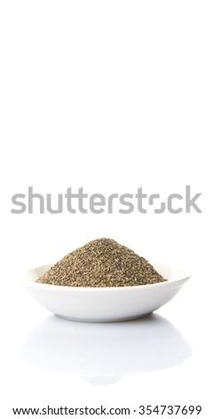 Black pepper powder in white bowl over white background - stock photo