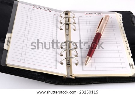 Black personal diary with red pen isolated on white