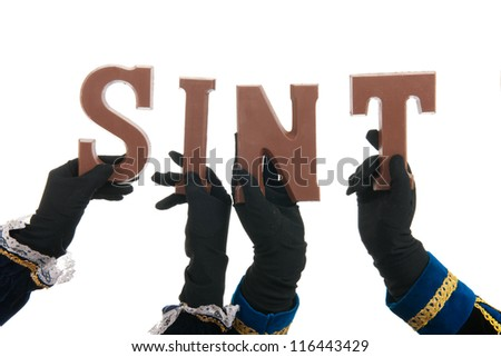 Black petes are writing Sint with chocolate letters - stock photo