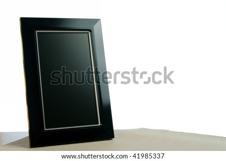 black photoframe on the table in white background - stock photo