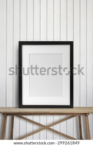 Black picture frame with on wooden table - stock photo