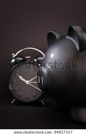Black Piggy Bank with alarm clock, Black Friday concept - stock photo