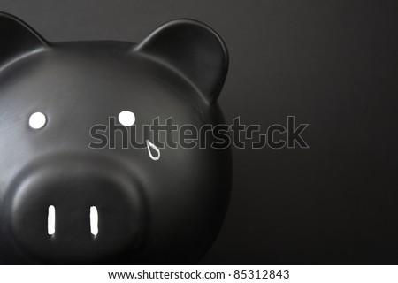 Black Piggy Bank with tear - stock photo