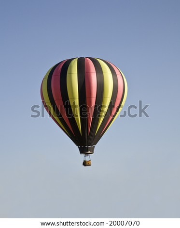 Black, pink and green hot air balloon against a clear sky.