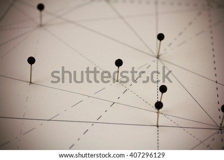 Black pins in paper linked together by lines
