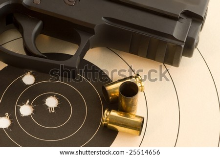 Black Pistol over paper target with bullet holes, bulls-eye and empty cartridge shells. - stock photo