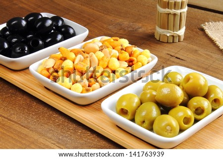 Black pitted olives, mixed nuts and stuffed green olives, a traditional aperitif - stock photo