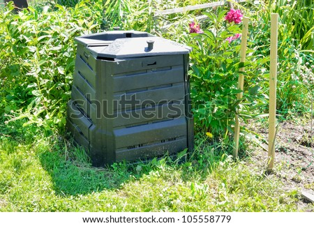 Black plastic compost bin in allotment garden - stock photo