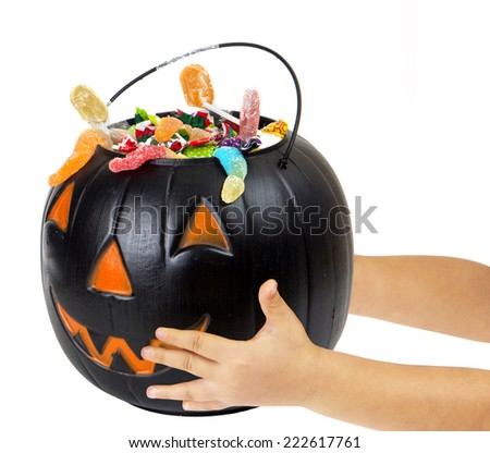 Black plastic pumpkin filled with candy and hand of kid - stock photo