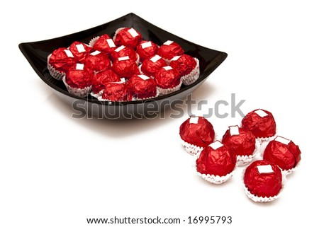 black plate and chocolate in red cover - stock photo