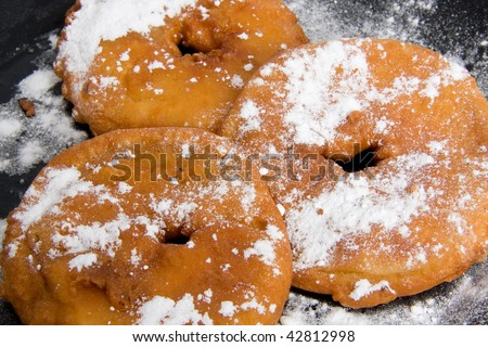 Black plate home baked with appelflappen ( apple fritters), typical dutch food  on New years eve. isolated on white background