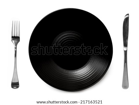 Black plate isolated on white with knife and fork.   - stock photo
