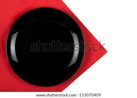 Black plate on red napkin - stock photo