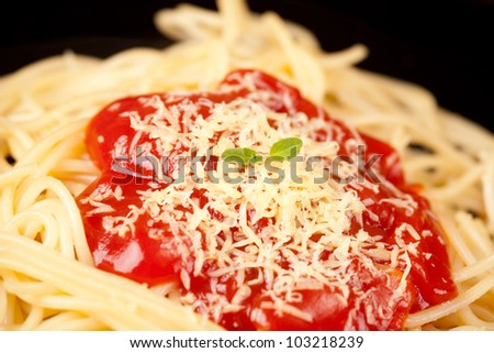 black plate with pasta on table - stock photo