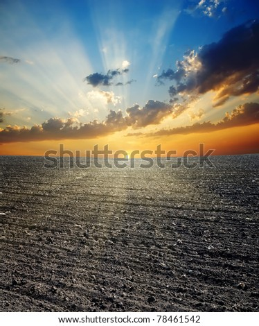 black ploughed field and sunset - stock photo