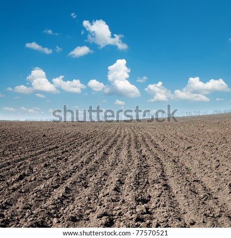black ploughed field under blue sky - stock photo