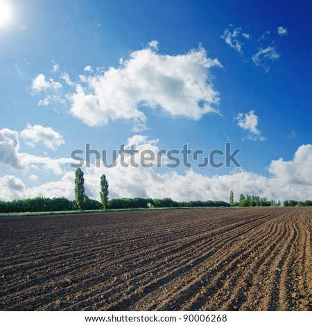 black ploughed field under blue sky with sun - stock photo