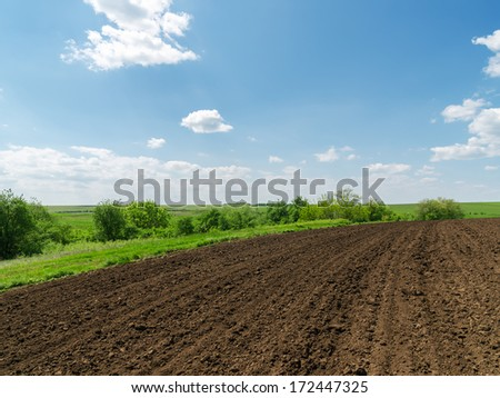 black plowed field and blue sky with clouds - stock photo