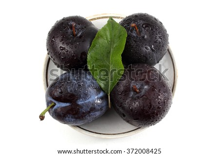 Black plums on dish