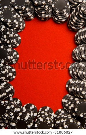 Black poker chips on red felt with copy space - stock photo