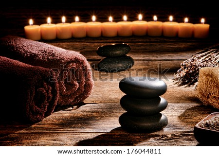 Black polished smooth hot massage stones in a Zen inspired cairn on a vintage wood boards table in a rustic natural and holistic spa for a traditional relaxation and health rejuvenation treatment - stock photo