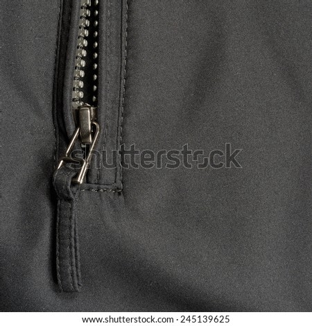 Black polyester twill fabric texture background, open jacket zip - stock photo