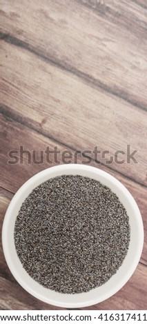 Black poppy seeds in white bowl over wooden background