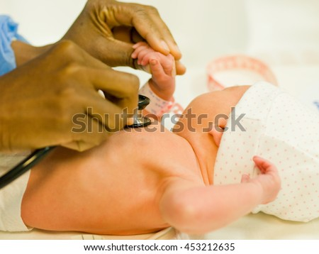 Black professional pediatrician is listening baby's heart