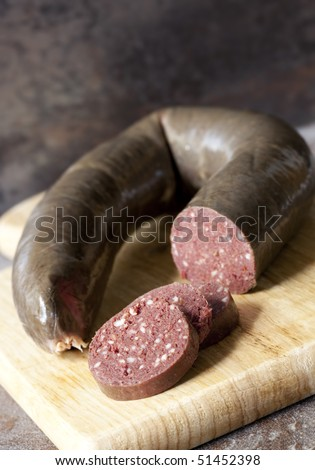 Black pudding, with cut slices, on chopping board over stone background.