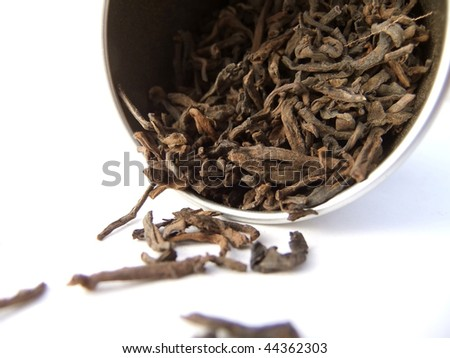 Black puerh tea cascading from silver canister - stock photo