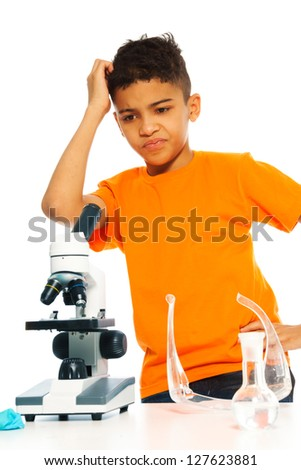 Black puzzled boy in chemistry class with microscope and lab glass equipment - stock photo