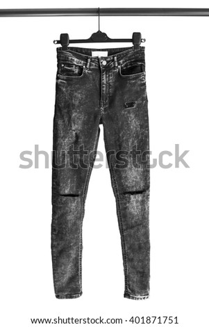 Black ragged jeans on clothes rack isolated over white - stock photo