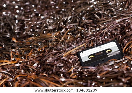 Black recordable plastic audio cassette resting on a large amount of magnetic audio tape. Selective focus on foreground. - stock photo