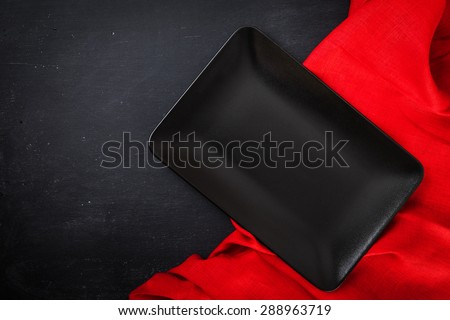Black rectangle plate with red napkin on black wooden table. Table laying. Top view. - stock photo