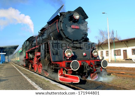 black red steam train with smoke, Poland - stock photo