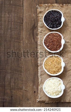 Black, red wild rice, basmati and unpolished whole rice in bowls on wooden table - stock photo